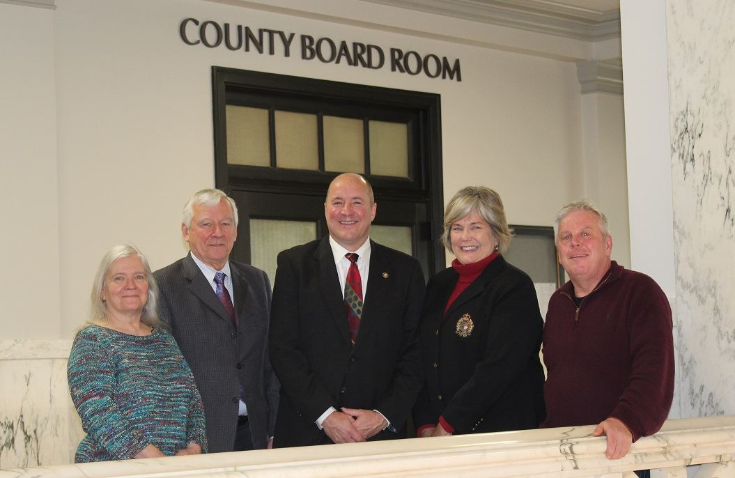 Picture of all five Crow Wing County Commissioners standing in front of the Crow Wing County Board R