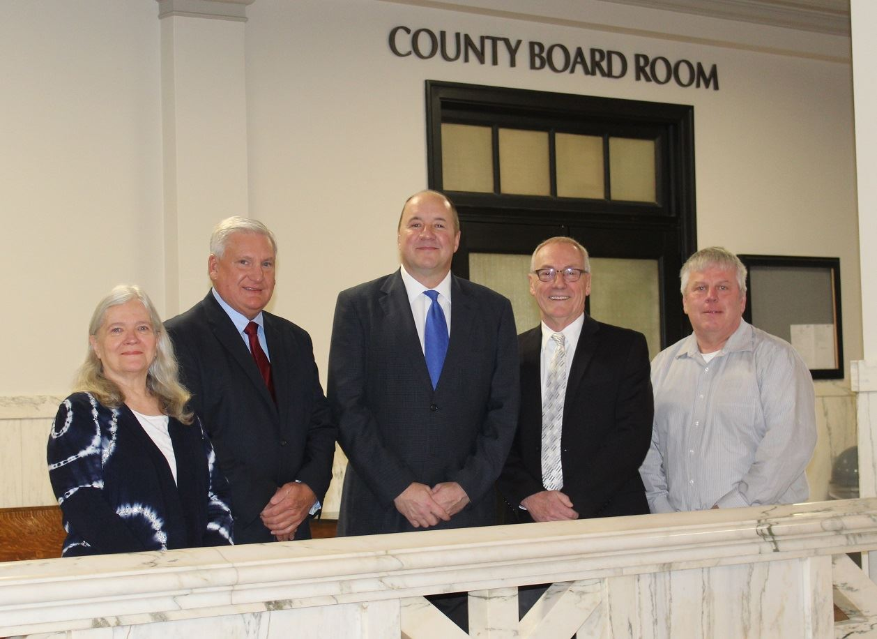 All five Crow Wing County commissioners posing for a picture in front of the county board room door