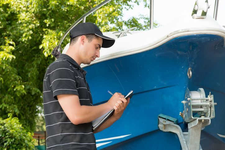 Person inspecting a boat and making notes
