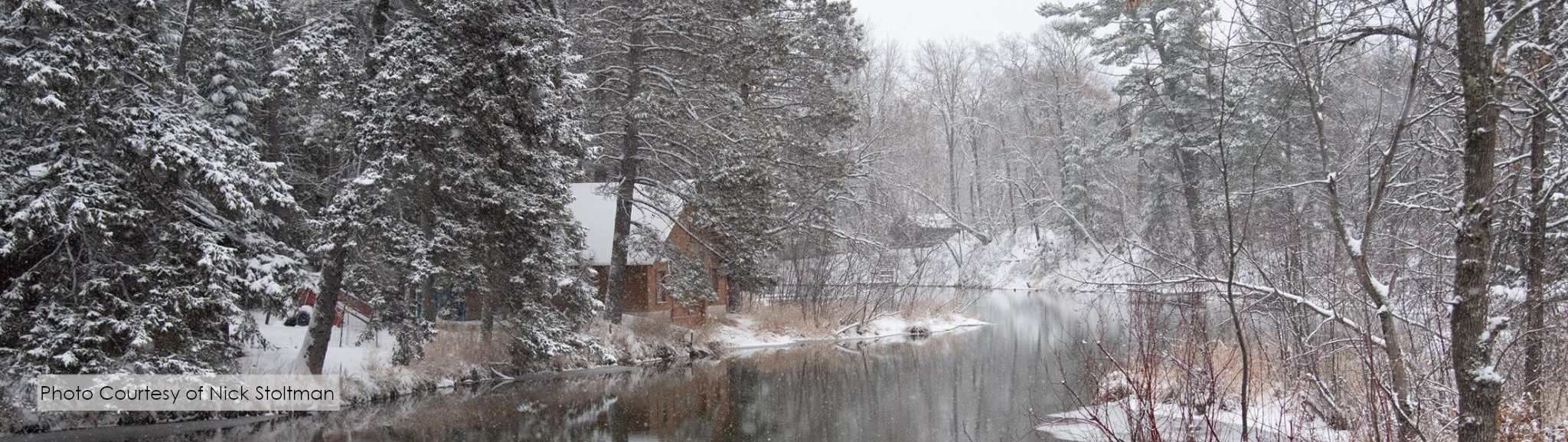 A cabin along an open stream in a snow covered forest